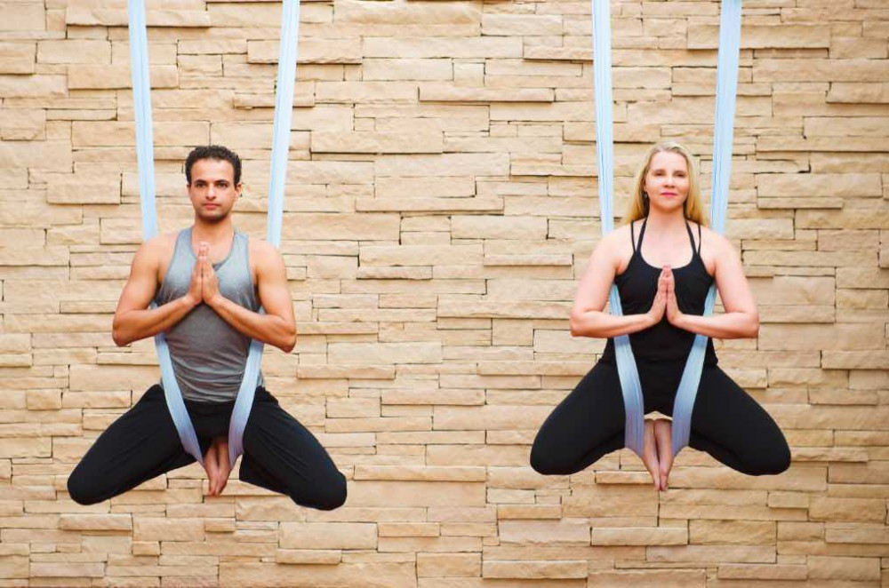 man and woman practising aerial yoga
